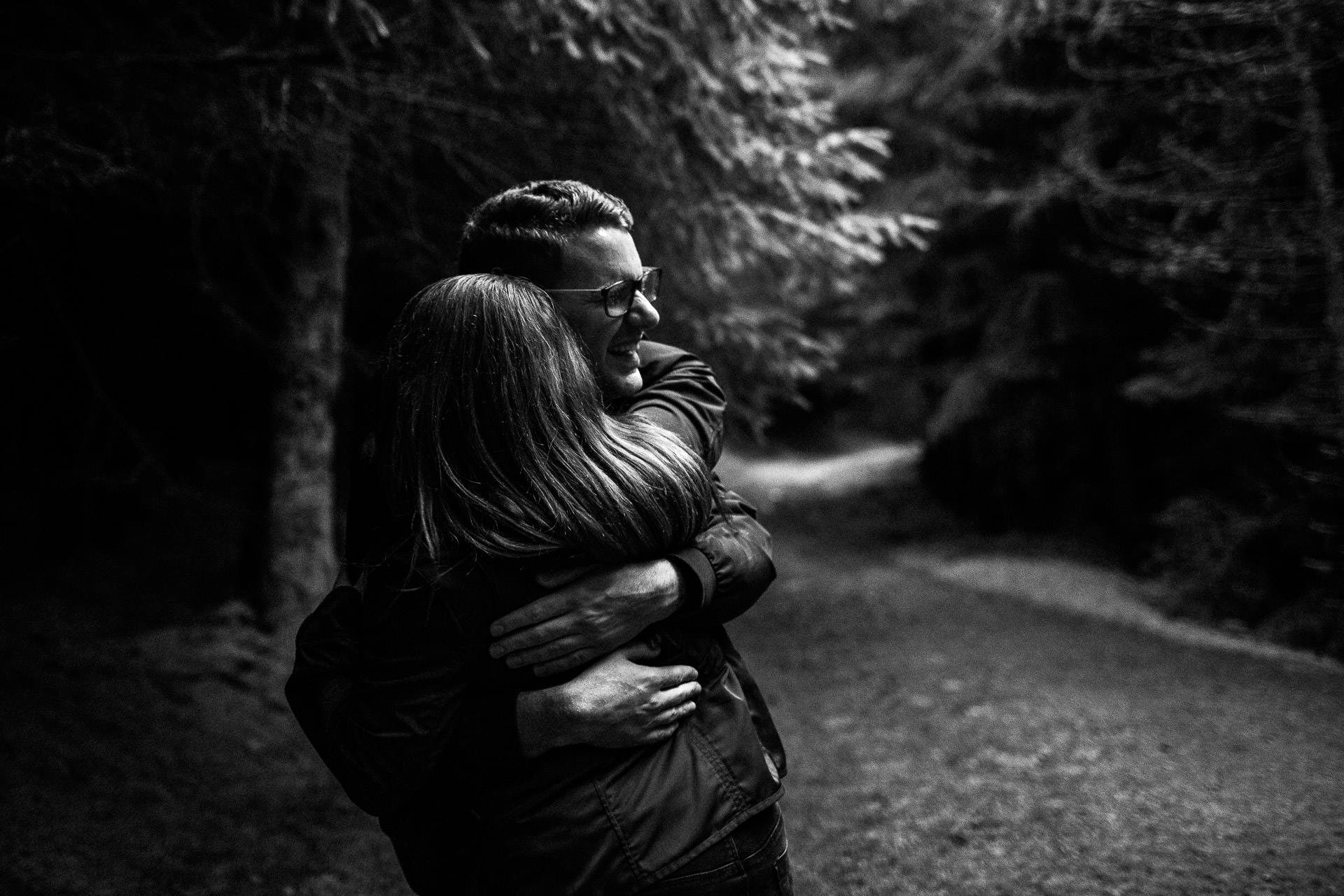 Whinlatter Pre Wedding Shoot Lake District - N&P - black and white of couple hugging in the trees
